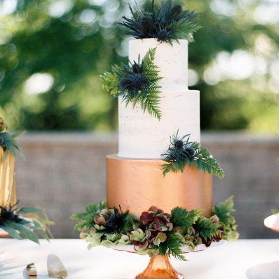 a color block wedding cake with a copper and white layers plus lush tropical greenery