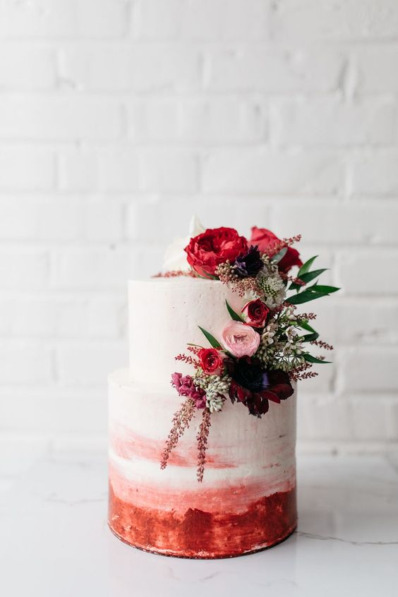 a bright ombre wedding cake in white to pink plus red, pink ad burgundy blooms and greenery
