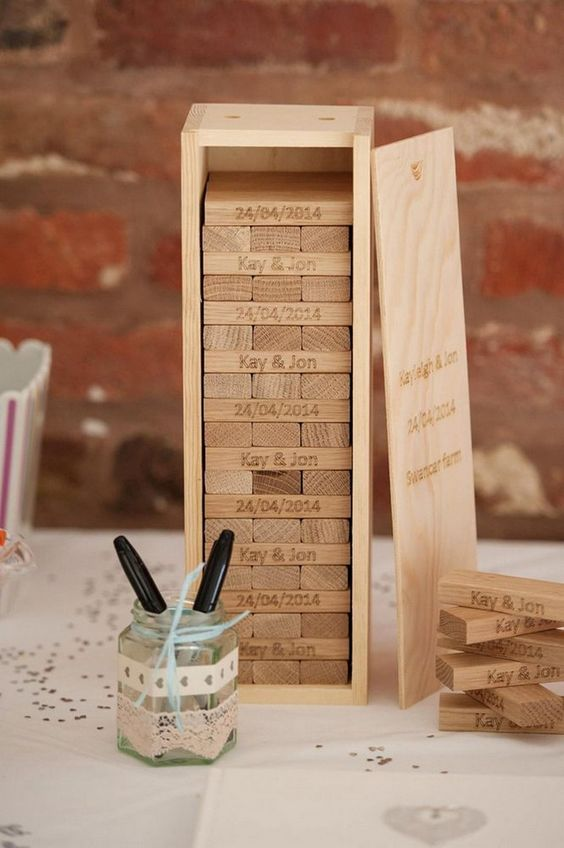a wooden box with wood pieces that are to be signed by the guests and a lid to store them comfortably