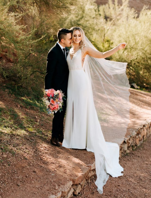 The bride was wearing a Sarah Seven gown with a lace bodice, a plain skirt with a front slit and a veil