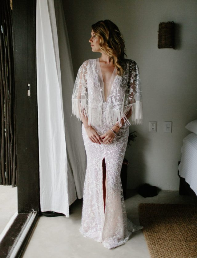 a glam boho gown with lace appliques, a plunging neckline, a front slit and long fringe on the bell sleeves for more chic