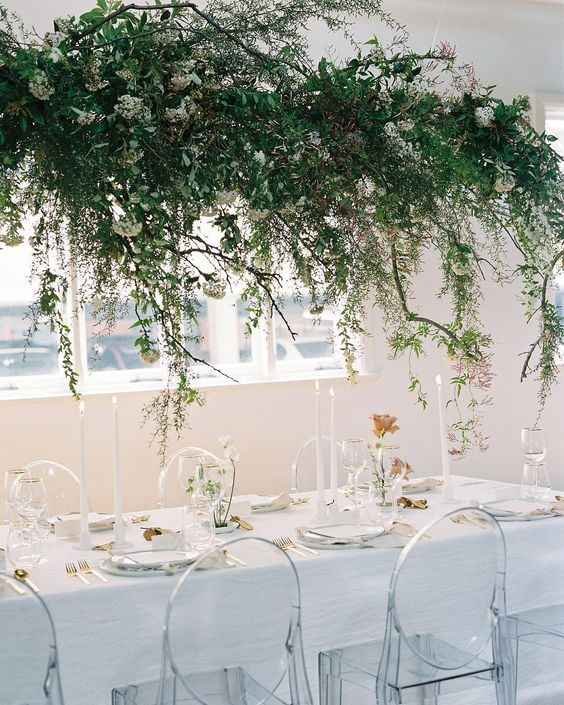 a lush greenery and white bloom wedding installation over the reception table for a refershing spring feel
