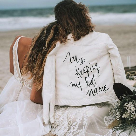 a white leather jacket with a fun inscription is a cool idea to wear for your wedding or for some shots