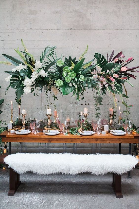 a lush tropical wedding installation with tropical leaves and blooms and some cascading greenery