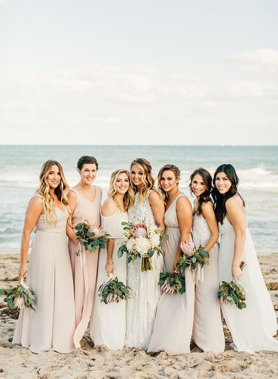mismatching neutral beach bridesmaid dresses in cream and blush, with various designs and necklines