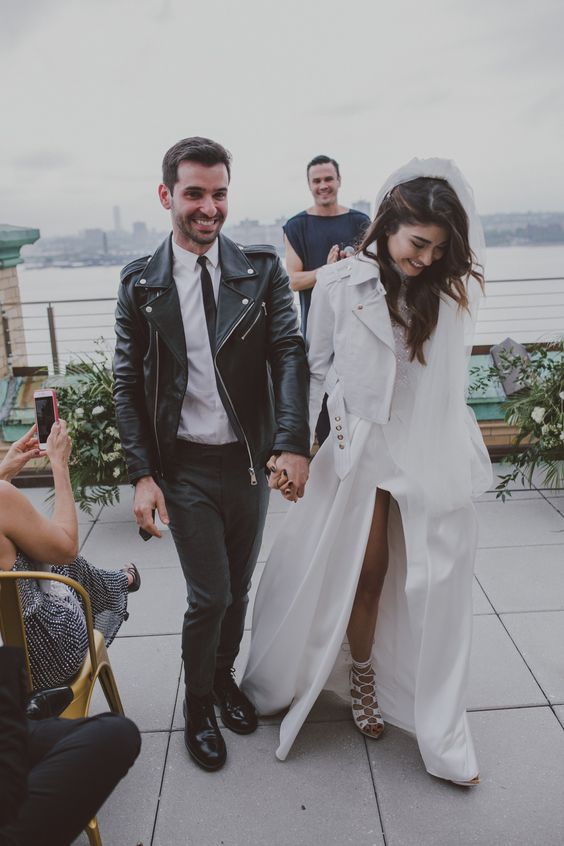grey pants, a white shirt, a black leather moto jacket, black shoes for a modern and hot groom's look
