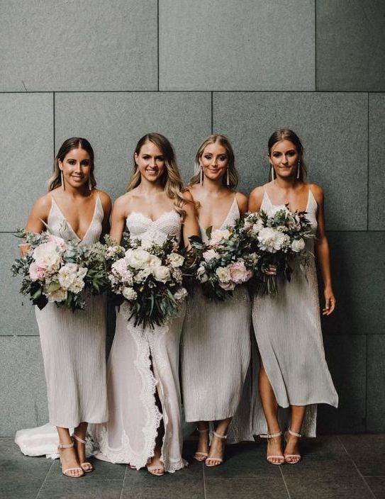 shiny silver high low midi bridesmaid dresses with thick straps and pluning necklines and statement earrings