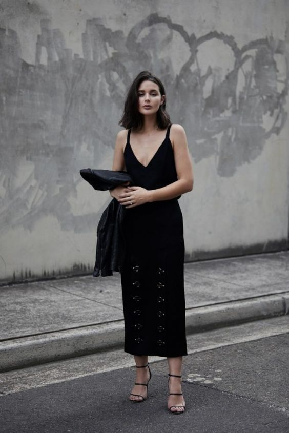 a black strip V-neckline top, a statement black midi skirt with detailing, black strappy heels and a black moto jacket