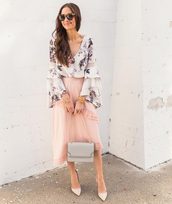 a blush ruffled asymmetrical midi, a floral blouse with bell sleeves, neutral shoes and a grey bag