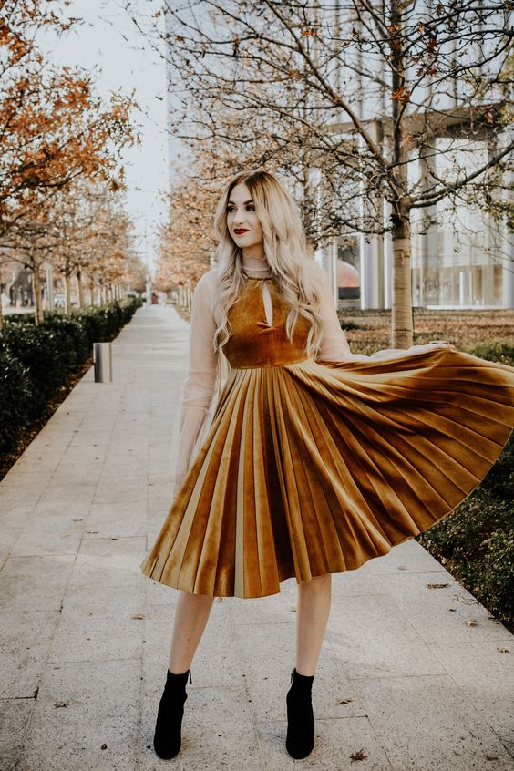 a mustard velvet A-line dress with a halter neckline and a pleated skirt is perfect for a spring wedding guest look with black booties for a fall wedding
