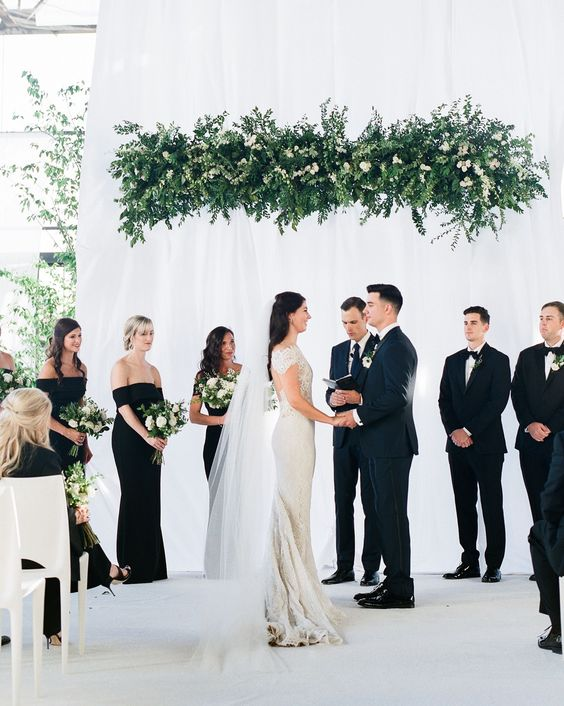 an overhead greenery and white bloom wedding installation as a wedding ceremony backdrop