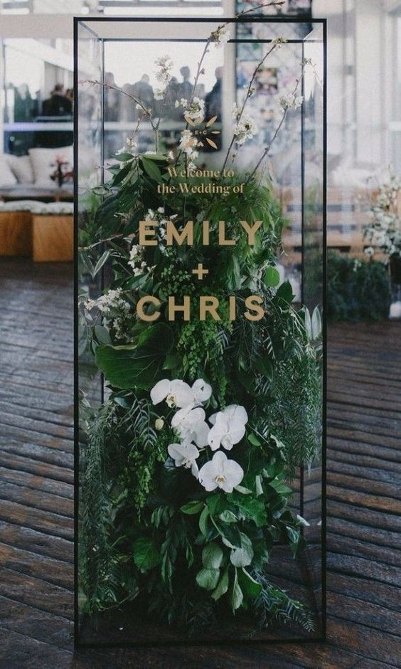 a minimalist cube with fresh greenery and white orchids as a welcome sign is a unique and bold decor idea