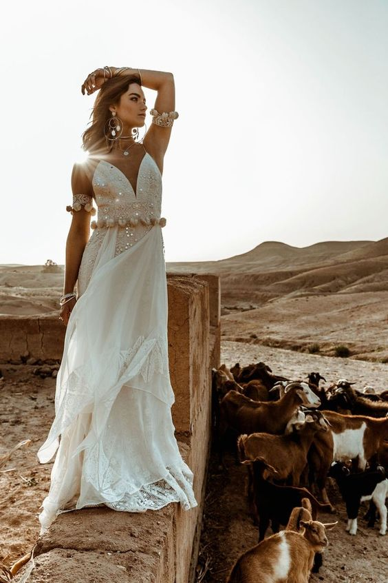 a shiny boho lace wedding gown with gold pompoms on the waist and matching pompom arm band sleeves