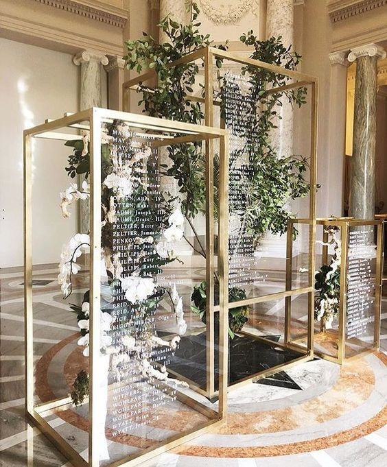 floral and greenery installations in gilded frames with wedding signage is a modern adn fresh idea of a seating chart