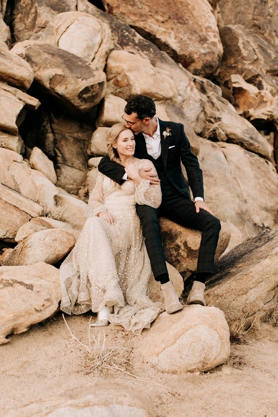 a black plaid three-piece wedding suit with a white shirt and no tie plus tan boots to walk in the desert