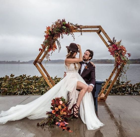 a bright fall hexagon wedding arch with dried leaves in burgundy and rust, greenery and blooms