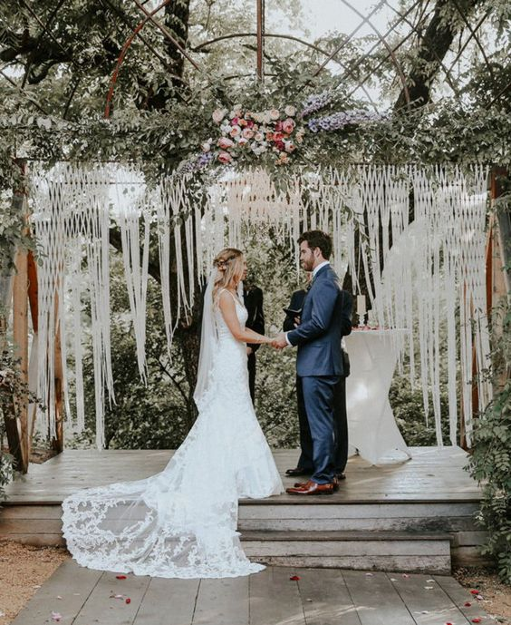 a chic macrame wedding backdrop with long fringe, lush greenery and pink blooms on top for a summer wedding