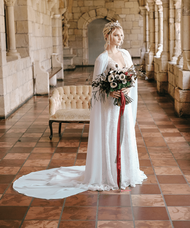 Daenerys inspired bridal look with a lace sheath wedding gown with a plunging neckline, a white coverup with a train and a crystal crown