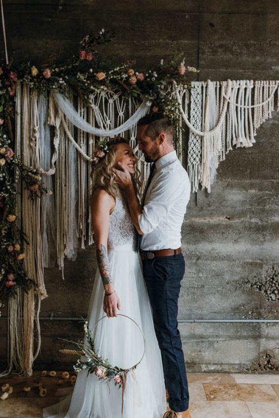 a gorgeous macrame wedding backdrop with greenery and fresh blooms on top feels very free-spirited