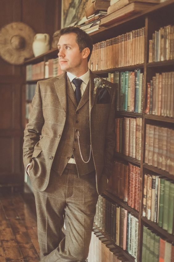 a brown three-piece windowpane suit, an off-white shirt, a black tie and handkerchief plus a chain for a vintage groom's look