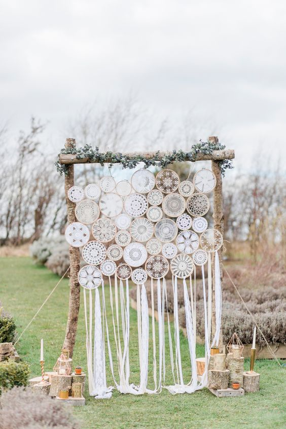 a rustic boho wedding backdrop made up of macrame dreamcatchers, greenery and candles around