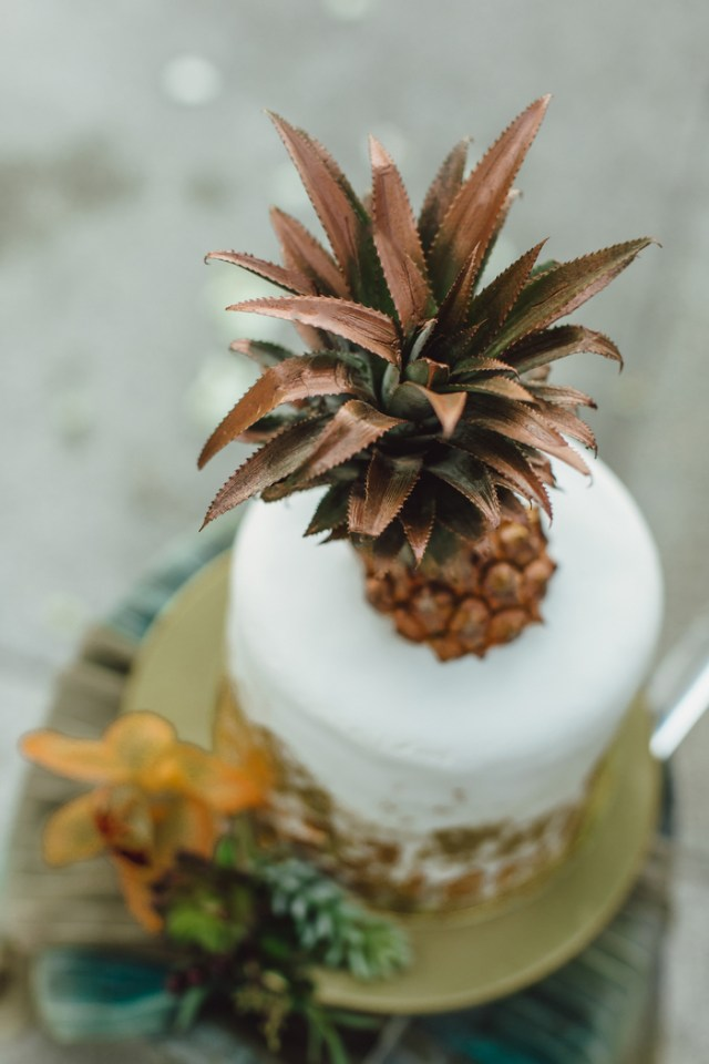 The wedding cake was a white one decorated with copper and with a copper pineapple topper
