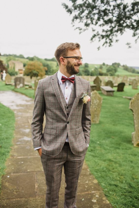 a stylish checked beige three-piece suit, a white shirt with copper buttons, a burgundy bow tie