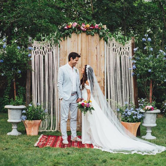 a wedding backdrop made of vintage doors, macrame and some greenery and bright flowers on top