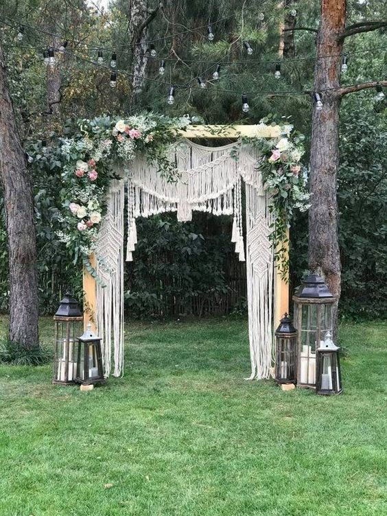 a boho macrame wedding arch with lush blooms and greenery on top plus candle lanterns around