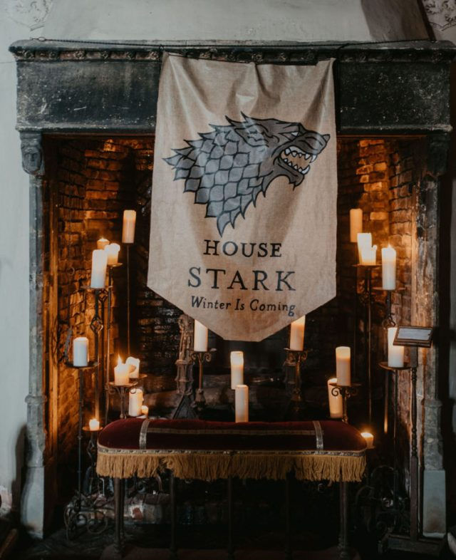 a unique wedding backdrop with a fireplace with candles, a velvet seat and a Stark flag