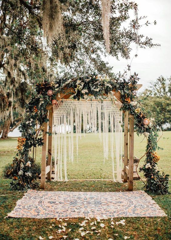 a boho wedding arch with macrame and fringe, lush greenery and pink and white blooms