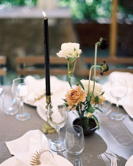 a delicate floral arrangement of a black vase, white and dusty pink blooms and a black candles in a gold candle holder