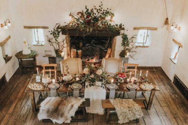 luxurious venue decor with textural greenery, fruits and blooms, candles and faux fur plus delicious food