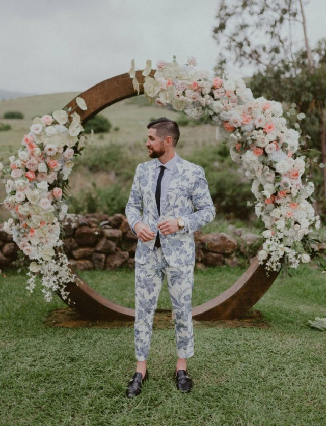 a blue floral print suit, a white shirt, a black tie and black shoes with no socks for a summer groom