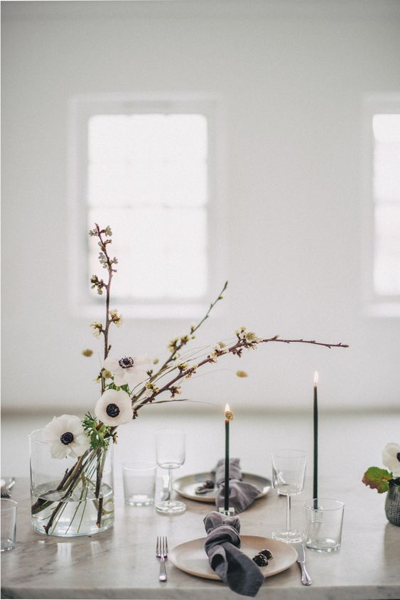 a large clear vase with blooming branches and white anemones is highlighted with thin black candles