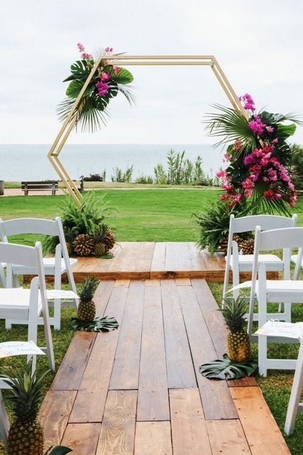 a tropical hexagon wedding arch decorated with tropical leaves, bright pink florals and tropical fruits at the base