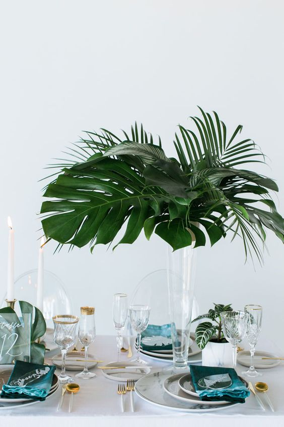 a minimalist tropical wedding centerpiece with a tall clear vase and some cute tropical leaves is a chic idea for a minimal wedding