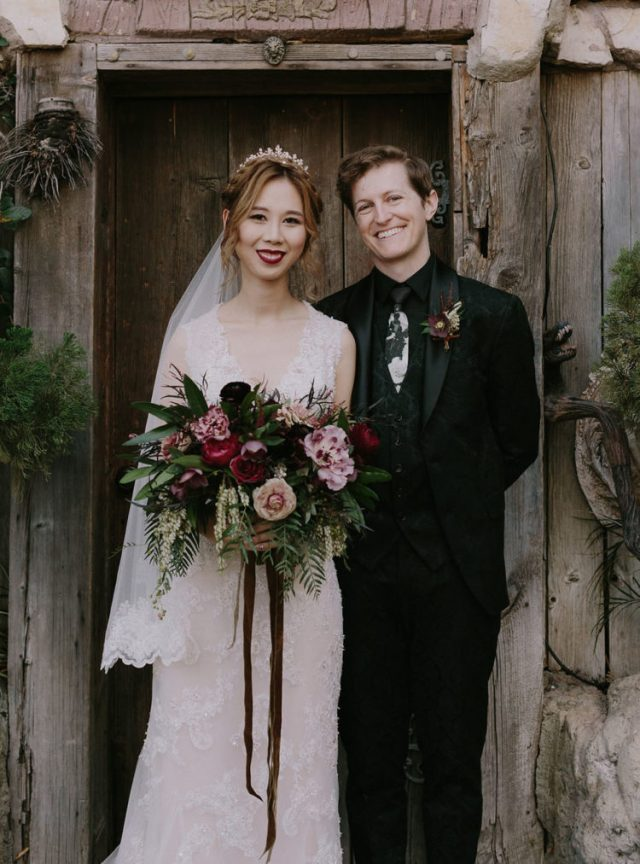 a black floral print three-piece suit, a matching printed white tie and a dark floral boutonniere for a Halloween groom