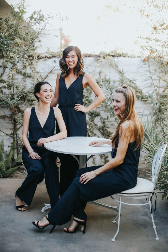 stylish and simple navy modern jumpsuits with deep V-necklines and black heels for modern bridesmaids