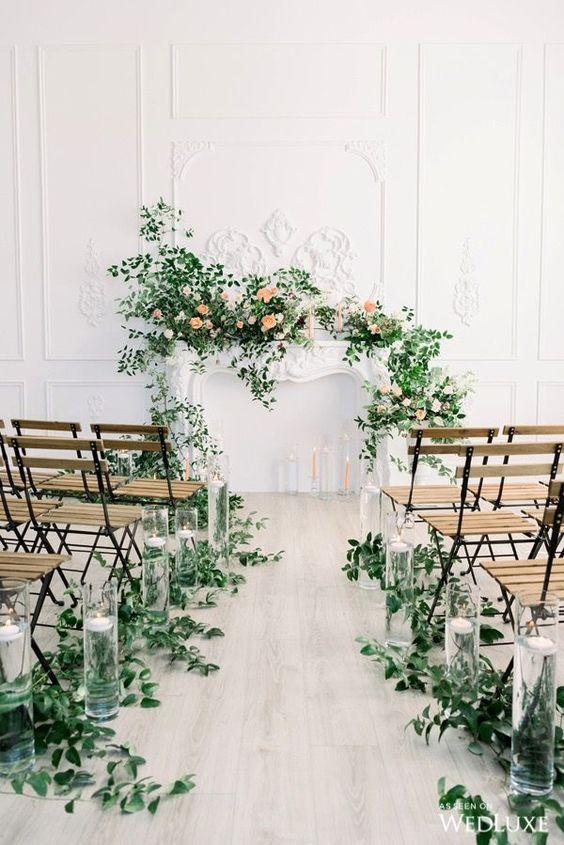 a gorgeous wedding ceremony space with greenery on the aisle and greenery and blooms on the faux mantel