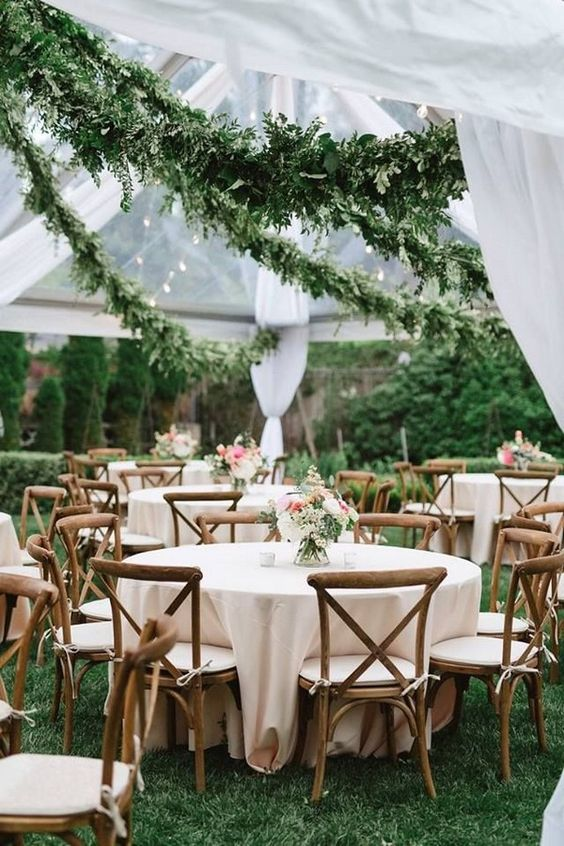 lush greenery garlands over the reception make the space stunning and you won't need much money