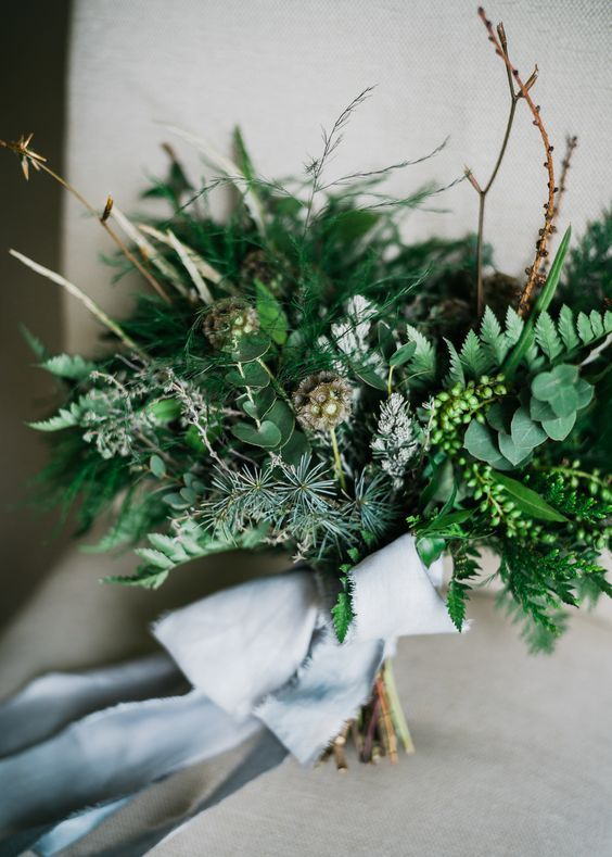 a lush and textural greenery wedding bouquet and twigs plus blue ribbons is a chic idea