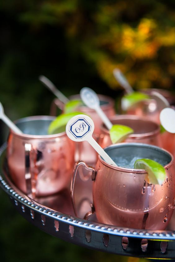 signature wedding drinks in copper mugs and with wooden drink stirrers with monograms