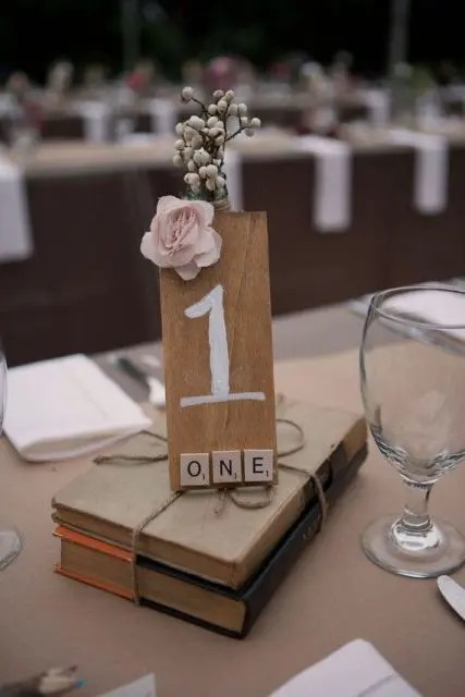 vintage books with a tie, a plywood table number and a pink bloom for a book lover wedding