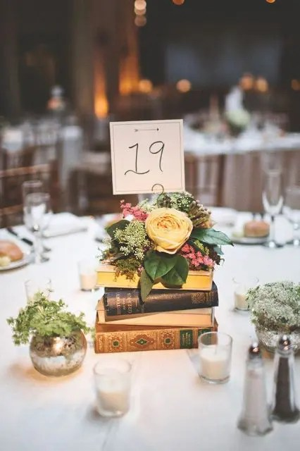 a book stack centerpiece with a bright floral arrangement on top and a table number plus some greenery around