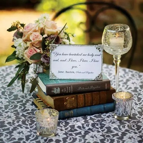 a vintage book wedding centerpiece with a quote, a candle in a glass and some blooms behind