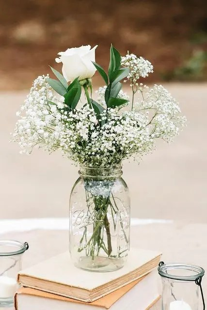vintage books with a white floral arrangement on top will always work for a rustic wedding or a vintage one