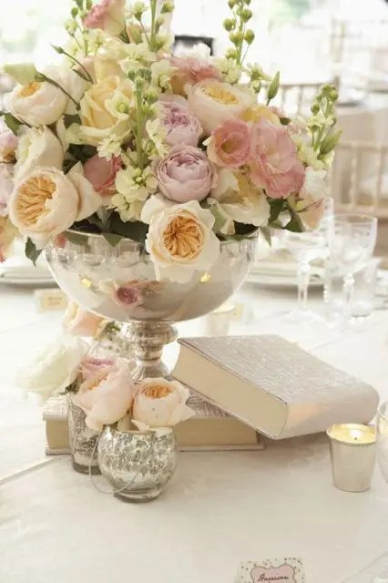 some books and a large bowl with a lush blush and iivory florla arrangement for a vintage-inspired wedding