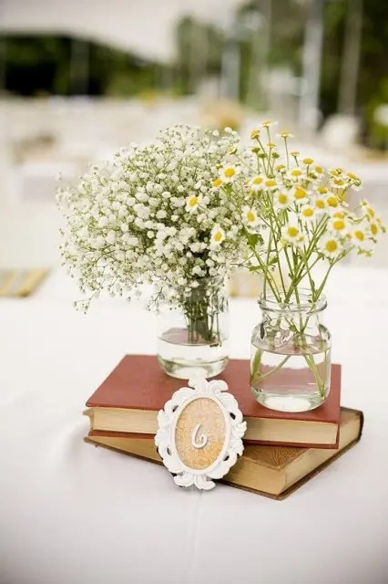 a book wedding centerpiece with a frame table number and clear vases with chamomiles and baby's breath