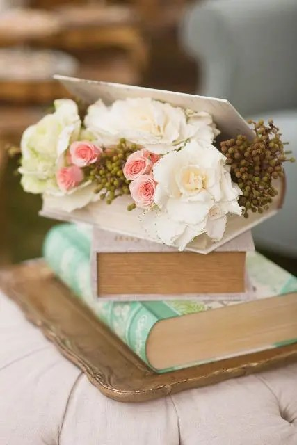 a stack of vintage books with fresh blooms inside is a gorgeous idea for a vintage or shabby chic wedding